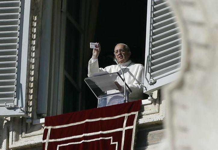 Como si se tratara de una caja de medicinas, el Papa mostró desde la ventana de su estudio una caja que contenía un rosario. (Agencias)