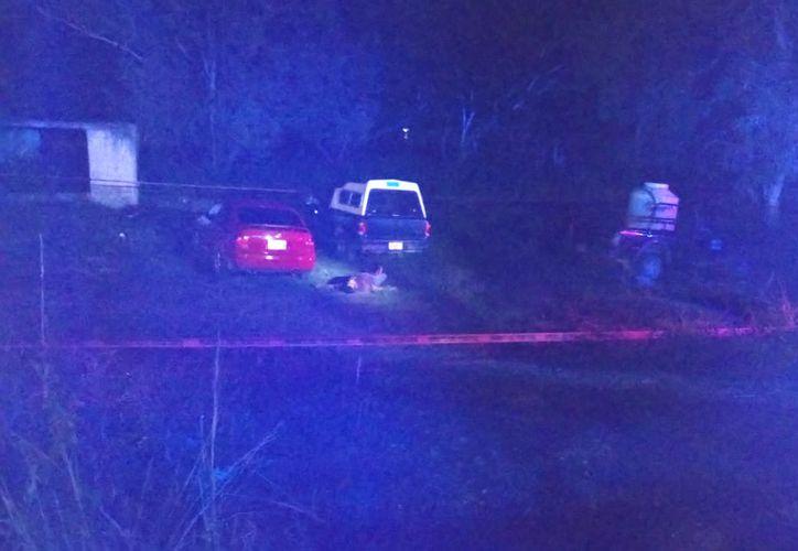 Los cuerpos quedaron tirados junto al auto al que pretendía subir. (Redacción/SIPSE)