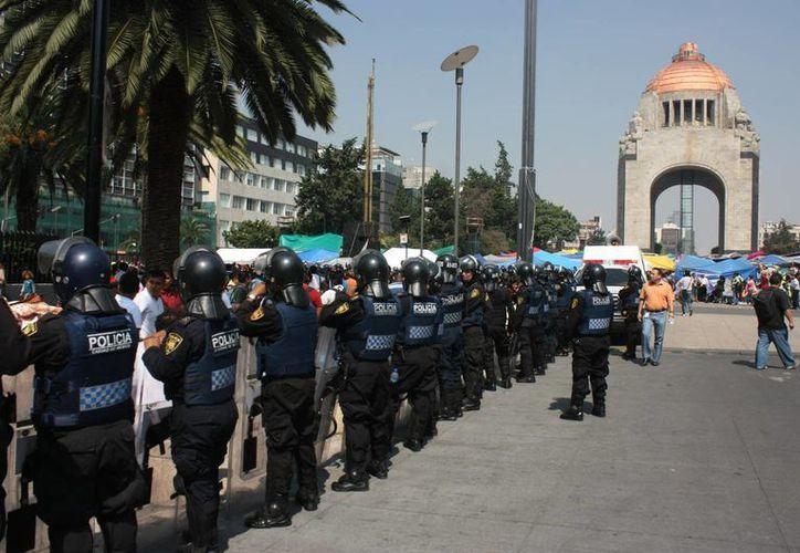 La Canacope estima pérdidas por más de 2 mil mdp en casi dos años de la presencia de la CNTE en el DF. En la foto, plantón en el Monumento a la Revolución, bajo la vigilancia policiaca. (Notimex)