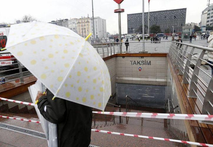 Un vendedor callejero ofrece paraguas delante de una estación de metro cerrada tras un incidente en la plaza Taksim, Estambul, Turquía. (Archivo/EFE)
