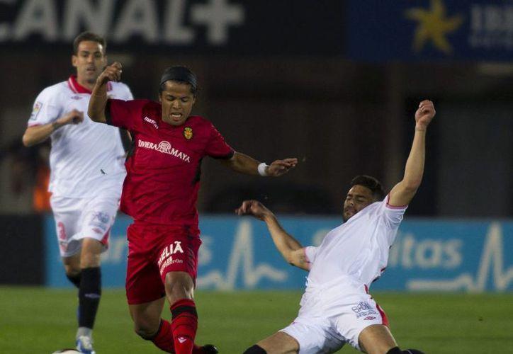 El delantero mexicano del Mallorca Giovani Dos Santos y el defensa del Sevilla FC, Alberto Botía, luchan por el balón durante el partido disputado en el Iberostar Estadio de Palma. (EFE)