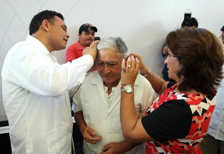 El gobernador Rolando Zapata Bello y la presidenta del DIF Yucatán, Sarita Blancarte, colocan un aparato auditivo a uno de los beneficiarios. (SIPSE)