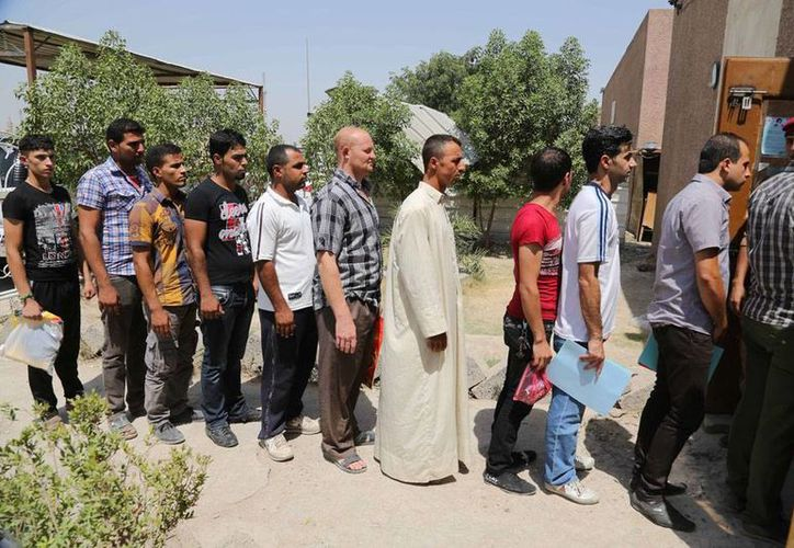 Entre las víctimas de los enfrentamientos entre grupos chiíes y suníes había tres 'voluntarios' que tomaron las armas ante el avance de los rebeldes. En la imagen, ciudadanos hacen fila para enrolarse como soldados voluntarios. (AP)