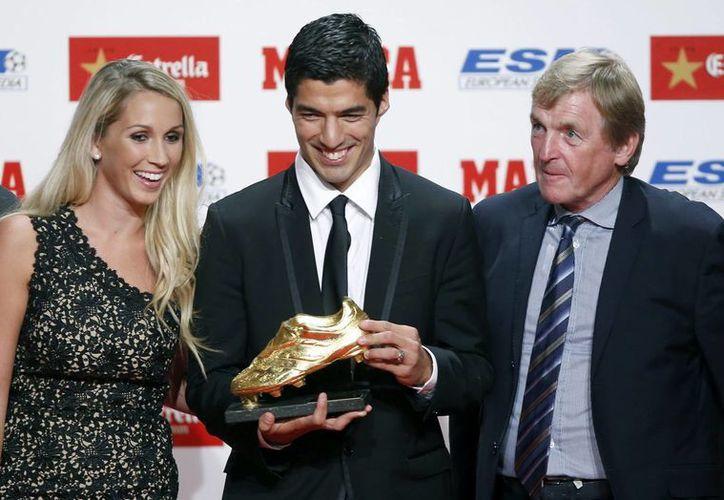 El delantero uruguayo del Barcelona, Luis Suárez (c), junto a su esposa Sofía Balbi y el exjugador del Liverpool, Kenny Dalglish (d), muestra la Bota de Oro de la temporada 2013-14. (EFE)