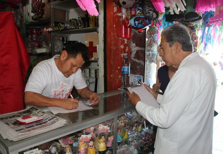 Maximiliano Vega Tato recorrió cada local del mercado para recaudar firmas. (Tomás Álvarez/SIPSE)