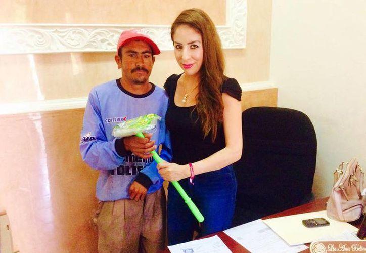 Imagen de la regidora perredista Ana Belinda Hurtado Marín al entregar un limpiaparabrisas a un hombre sin empleo. (Excelsior)