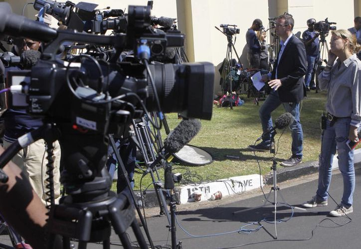 Periodistas hacen guardia en espera de la salida de Nelson Mandela del hospital de Pretoria, donde fue hospitalizado desde el 8 de junio pasado. (AP)