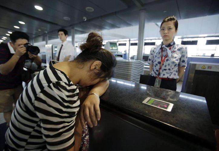 Un familiar de uno de los pasajeros muertos al enterarse de lo sucedido. (Agencias)