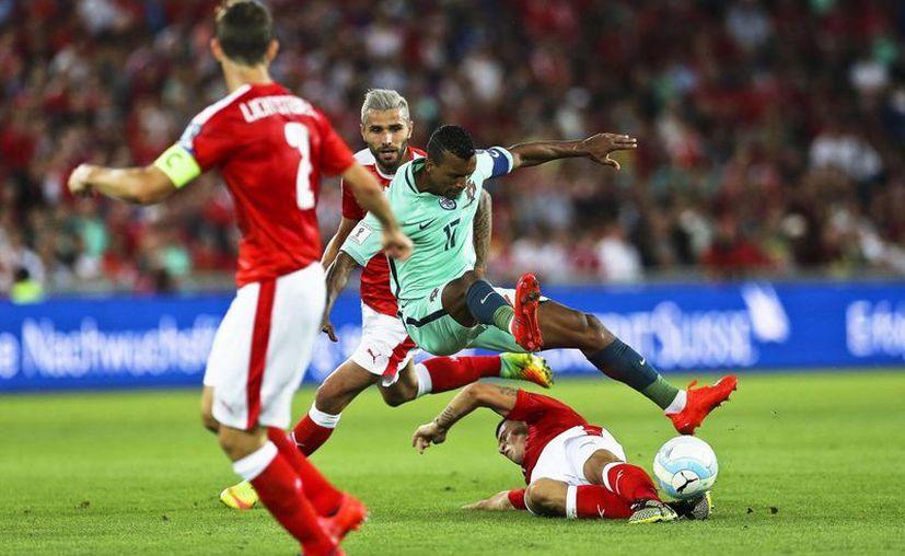El portugués Nani (c) en acción ante el suizo Valon Behrami (atras) durante el partido eliminatorio mundialista del grupo B entre Suiza y Portugal en el estadio St. Jakob-Park en Basel, Suiza. (EFE)