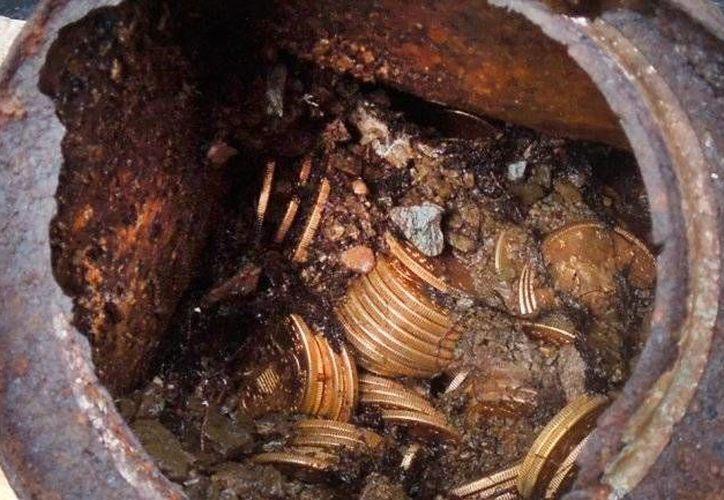 Foto de contexto de monedas de oro ocultas en una lata, similar al tesoro que encontró un meridano en terrenos de Cordemex. (Agencias)