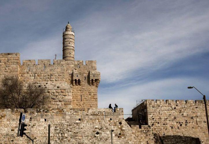 Fotografía de archivo del 2012, donde se observa a una pareja sentada junto a la Torre de David, sobre el muro que rodea la ciudad vieja de Jerusalén. (Agencias)