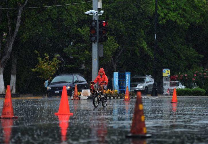 Un niño en la Bici-ruta en Paseo de Montejo disfrutó de la lluvia que duró cerca de 10 minutos. (SIPSE)