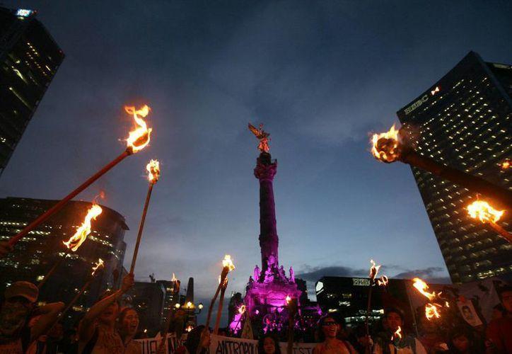 Miles de personas portaron antorchas durante la marcha hacia el Zócalo de la Ciudad de México exigiendo respuestas por la desaparición de los normalistas de Ayotzinapa. (AP)