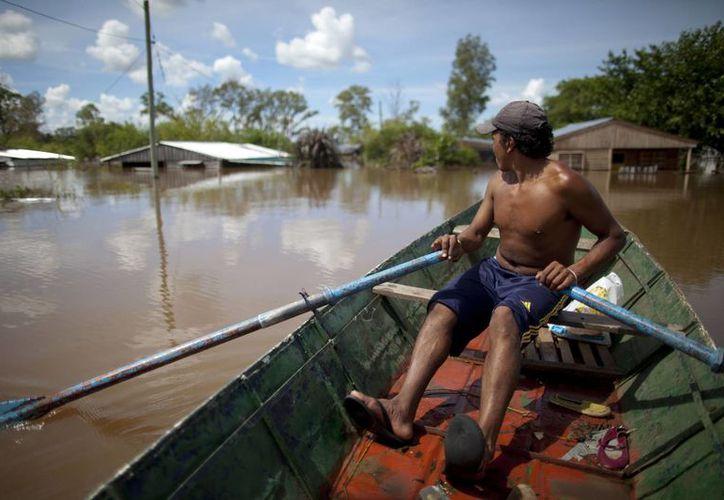 Debido a las inundaciones en Concordia, Argentina, la gente utiliza canoas para desplazarse debido a que el agua alcanzo los techos de las casas. (AP)