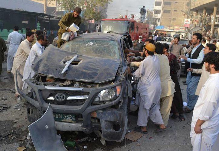 Los peatones tratan de rescatar a un herido atrapado dentro de un vehículo después de una explosión en Quetta. (Agencias)