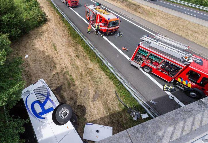 Unidades de bomberos y rescate acuden al lugar donde un autobús se salió de la carretera y dio un vuelco en Middlekerke, cerca de la costa de Bélgica. La unidad transportaba estudiantes británicos menores de edad. (AP Foto/Geert Vanden Wijngaert)
