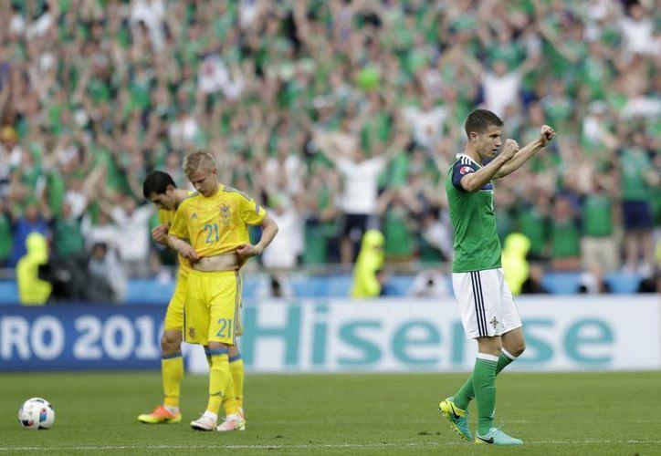 El futbolista Paddy McNair (der) de Irlanda del Norte celebra al final del partido, del Grupo C de la Euro 2016, en la que resultó ganador ante Ucrania, en el Grand Stade en Decines-Charpieu, cerca de Lyon, Francia. (Foto AP / Pavel Golovkin)