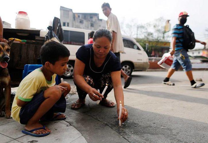 Personas colocan velas en el sitio donde fue asesinado un periodista, en Filipinas. (EFE)