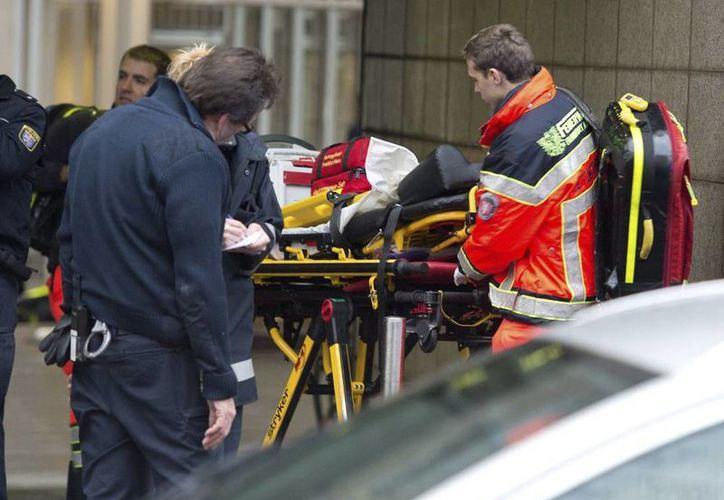 Un extranjero mató ayer a 2 personas frente a la sede de un juzgado en Fráncfort, Alemania. En la imagen, una de las víctimas, quien salió gravemente herido, es llevada al hospital, pero falleció durante el traslado. (Efe)
