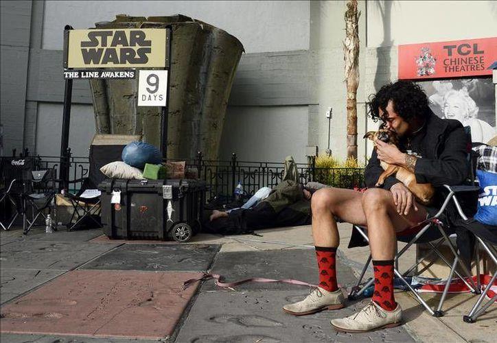 Fanáticos vestidos con disfraces y cargados de objetos alusivo a la saga de <i>Star Wars</i>, acampan afuera del Teatro Chino de Los Ángeles en espera del estreno de <i>El Despertar de la Fuerza</i>. (EFE)