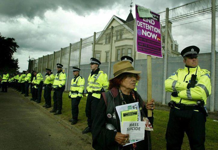 Una mujer protesta a las puertas del centro de detención de Dungavel en Escocia, una de las instituciones a las que son trasladados los inmigrantes y solicitantes de asilo. Policía británica rescata a 53 adultos y 15 niños migrantes en el puerto de Essex. (EFE/Archivo)