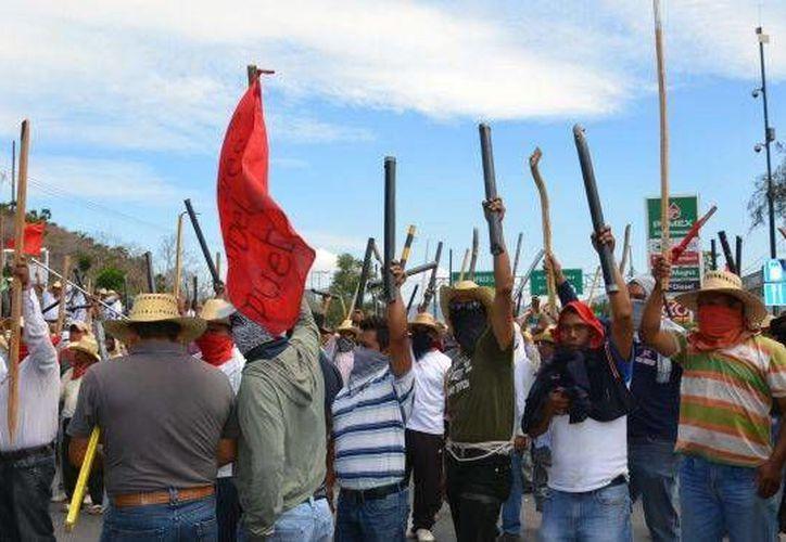 Millares de profesores marchaban por la capital del estado, algunos rostros cubiertos y armados con palos y tubos de metal en enfrentamiento contra la reforma educativa. (Agencias)