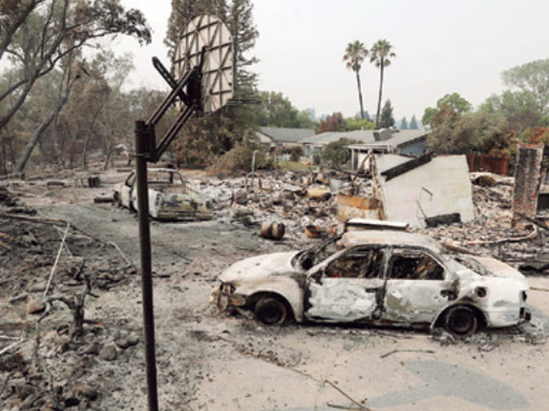 Burned vehicles sit in front of a wildfire-ravaged home, in Redding, Calif.