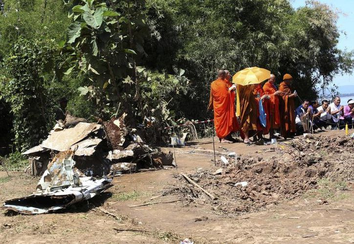 En la orilla del río, un grupo de monjes budistas realizó una ceremonia de oración por los ocupantes del vuelo QV301 de Lao Airlines. (Agencias)