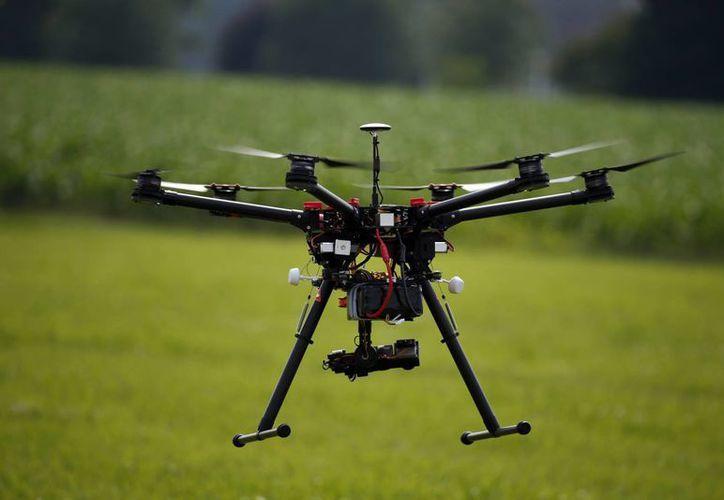 Bajo las nuevas reglas, los operadores deben registrar sus drones por internet. Un dron vuela en una granja y viñedo en Cordova, Maryland en una demostración de su uso para miembros de la junta de una organización agraria. (Agencias)