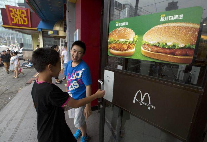 Imagen del 31 de julio pasado que muestra a unos niños entrando a un McDonald's en Beijing, China. La firma enfrenta en esta nación una crisis debido un escándalo por sus controles de  seguridad alimentaria. (Foto AP/Ng Han Guan, File)