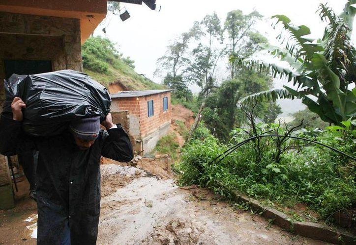 Un hombre retira las pertenencias de su casa, destruida por un deslizamiento provocado por las fuertes lluvias en Brasil. (EFE)