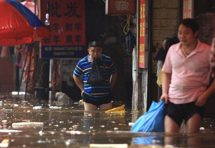 Civiles chinos caminan en medio de calles inundadas en Changsha, en el sur de la provincia de Hunan. (Foto: AP)