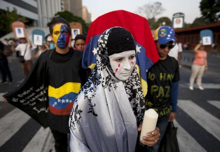 Un manifestante antigubernamental vestida como una viuda camina delante de un ataúd cubierto con la bandera de Venezuela en Caracas. (Agencias)