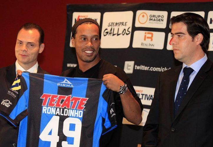 'Estoy contentísimo de estar aquí. Espero darles muchas alegrías', expresó el astro brasileño Ronaldinho en conferencia de prensa en las instalaciones del club Gallos Blancos de Querétaro. (Notimex)