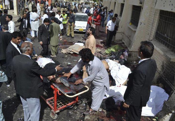 Un grupo de personas ayudan a los afectados por la explosión de una bomba en Quetta, Pakistán. (Agencias)