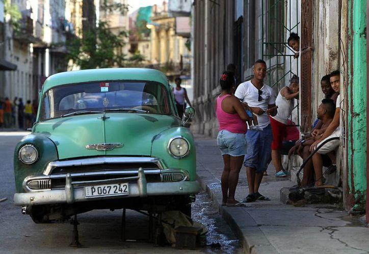 El programa Piramideo intenta a través de mensajes SMS facilitar la creación de redes sociales entre los cubanos. En la imagen, varias personas conversan junto a un viejo auto en La Habana, Cuba. (Archivo/EFE)