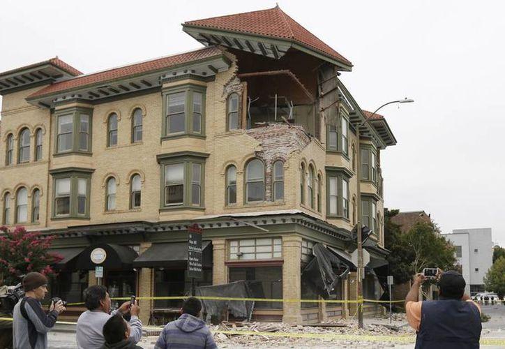Numerosas personas fotografían los daños estructurales de un edificio que se derrumbó parcialmente por el terremoto de este domingo en Napa, California. (Agencias)