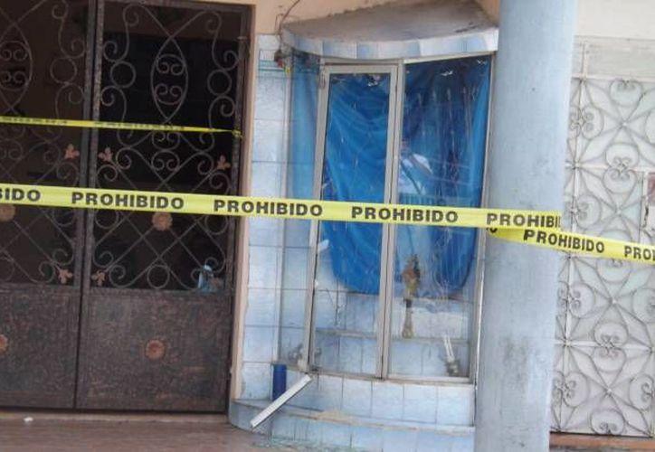 Los vidrios del nicho quedaron rotos debido al golpe que le dieron para sacar la imagen de la Virgen de Guadalupe, en el barrio de Santa Ana, en Valladolid. (Milenio Novedades)