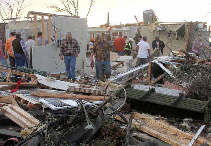 Vecinos inspeccionan una vivienda dañada por tormentas en Roundaway cerca de Clarksdale, Mississippi, el miércoles 23 de diciembre de 2015. Un sistema de tormentas dejó varios muertos a su paso por EU el miércoles. (Foto: AP/Troy Catchings)