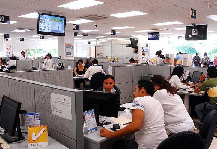 La nueva obligación fiscal para el pago de nómina entrará en vigor a partir del 1 de enero de 2017. Imagen de contexto de una oficina con sus empleados.  (Milenio Novedades)