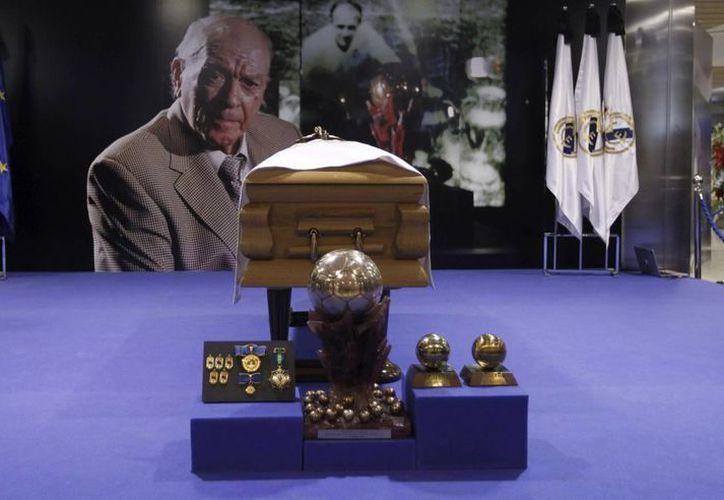 Toma frontal del féretro de Alfredo Di Stéfano, cubierto por una bandera del Real Madrid, y al fondo una imagen con su fotografía, flanqueado por banderas y flores. (EFE)