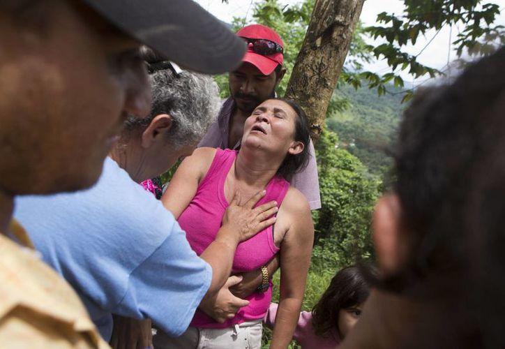 Una mujer es sostenida por un hombre mientras espera noticias de su hijo, uno de los mineros atrapados en la mina El Comal, en Bonanza, Nicaragua. (Agencias)