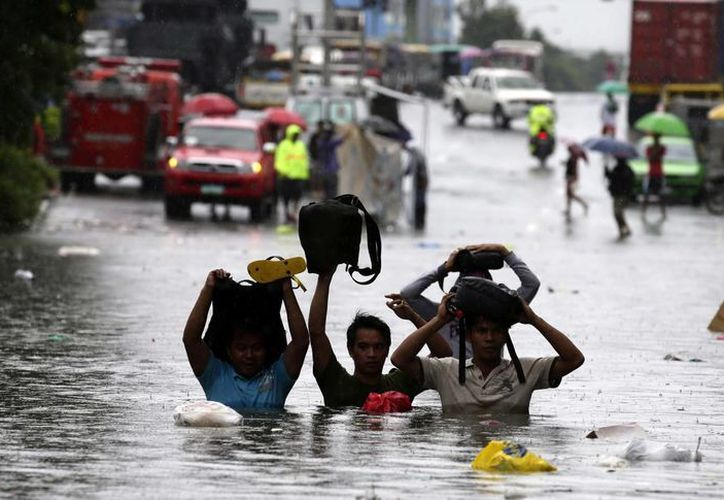 Un grupo de personas trata de no mojar sus pertenencias al cruzar una calle completamente inundada en Filipinas. (EFE)