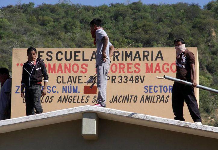 Padres de familia y docentes de la SNTE mantienen en su poder varias escuelas. La CNTE advierte que tomará medidas drásticas si el gobierno de Oaxaca no le entrega los planteles en disputa. (Archivo/Notimex)