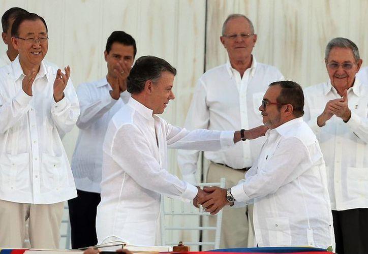 En el centro, el presidente Juan Manuel Santos y el líder de las FARC 'Timochenko' durante la histórica firma que pone fin al conflicto armado entre este país y el grupo guerrillero. (AP/ Fernando Vergara)