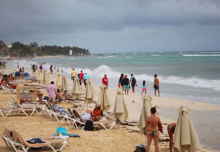 El turismo aprovechó la ausencia de lluvias y disfrutar la vista del oleaje en Playa del Carmen. (Daniel Pacheco/SIPSE)