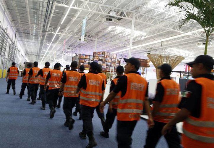 Cadetes de la Policía Federal en el momento en que se distribuyen en el interior del Lakám Center. (Israel Leal/SIPSE)