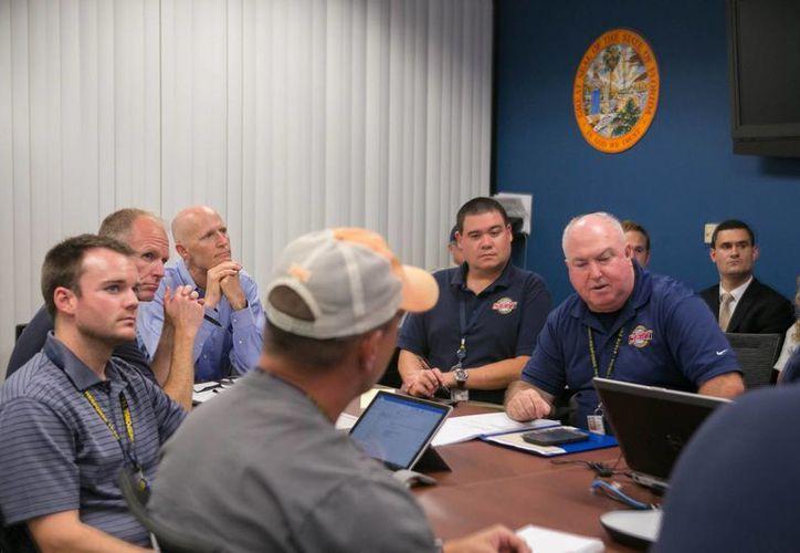 Fotografía cedida por la Oficina del gobernador Rick Scott (3-i) que muestra una reunión sobre el paso de la tormenta tropical Collin, en Tallahassee, Florida, EU. (EFE)