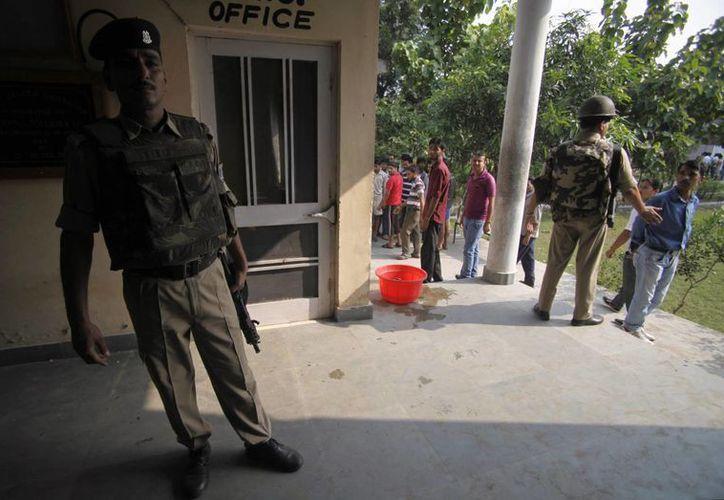 Soldados paramilitares indios montan guardia afuera de la estación de policía que fue objeto de un atentado. (Agencias)