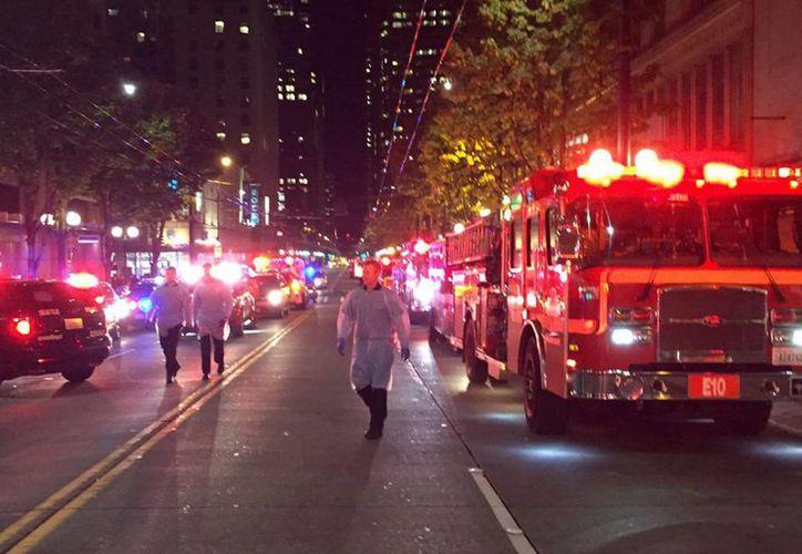 Fotografía facilitada por el Departamento de Bomberos de Seattle que muestra varios miembros de los servicios de emergencia desplegados en el lugar después de que cinco personas resultaran heridas en un tiroteo en el centro de Seattle. (EFE/Departamento de Bomberos de Seattle)